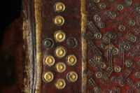 Az aranyozott bőrrátét kettőskör keret az oldalak sarkánál és felénél virág alakba rendeződik