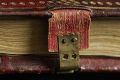 A lábmetszésnél levő, piros-aranysárga textilszalagra szerelt sárgaréz karmos csat