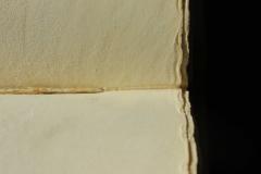 Az eredeti oromszegőalap rögzítőszálának lenyomata és szúráspontja az egyik ív közepén