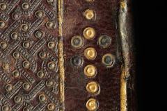 A táblák szélén végighúzódó aranyozott kettőskör-sor az oldalak felénél festett bőrrátétekkel egészül ki.