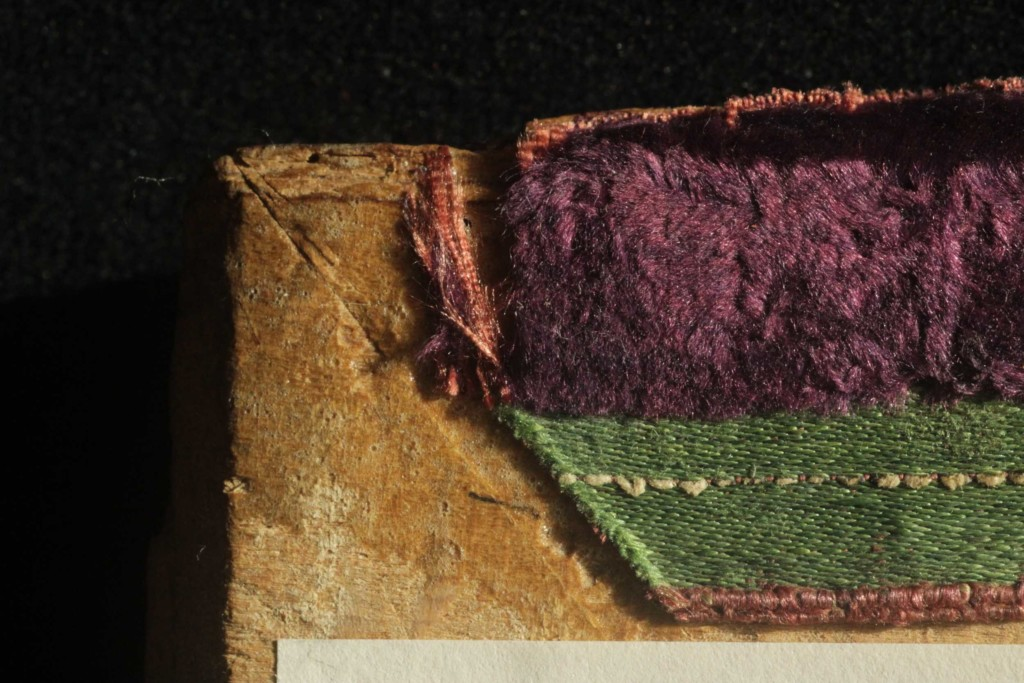 Intact, woven edge of the velvet on the fore-edge turn-in of the right board