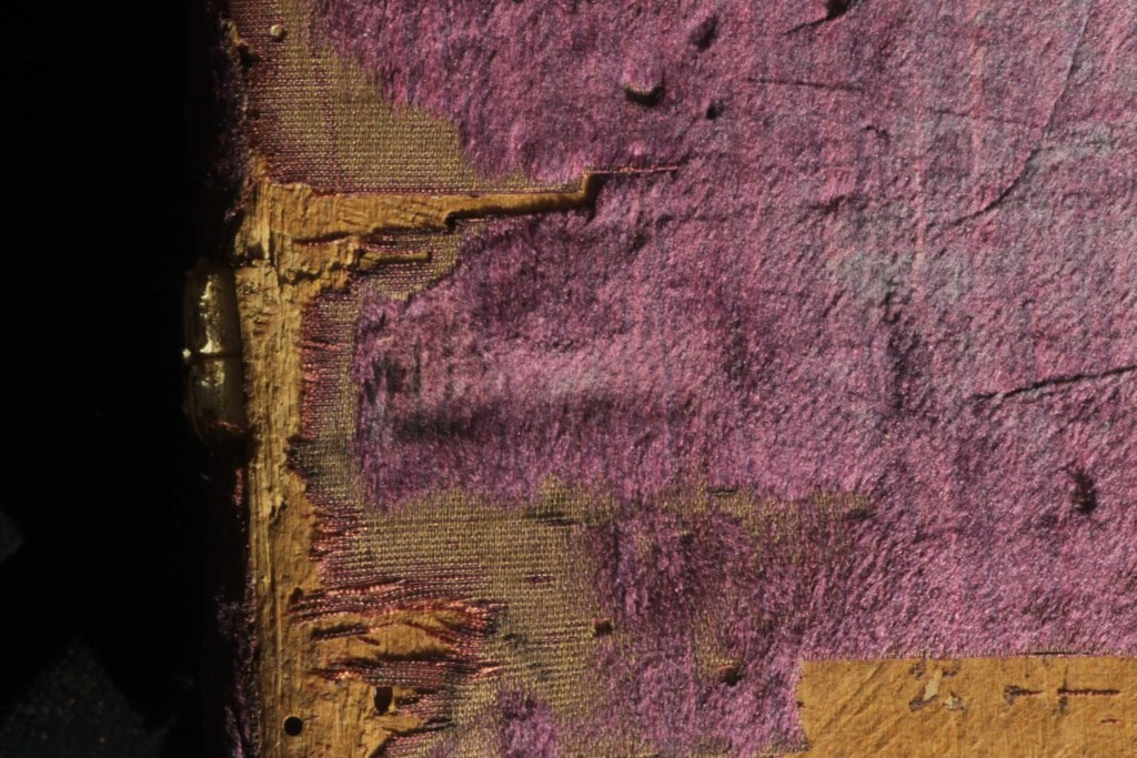 The contour of the sewing support recessed into the board is outlined on the velvet covering